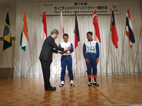 GM Honda Driving Safety Promotion Center Hidehiko Nakajima menyerahkan penghargaan kepada Ibnu Fachrizal (kiri) untuk raihan juara pertama kelas CB400 dan Overall Group CB400 di ajang The 19th Safety Japan Instructors Competition 2018 di Suzuka, Jepang.